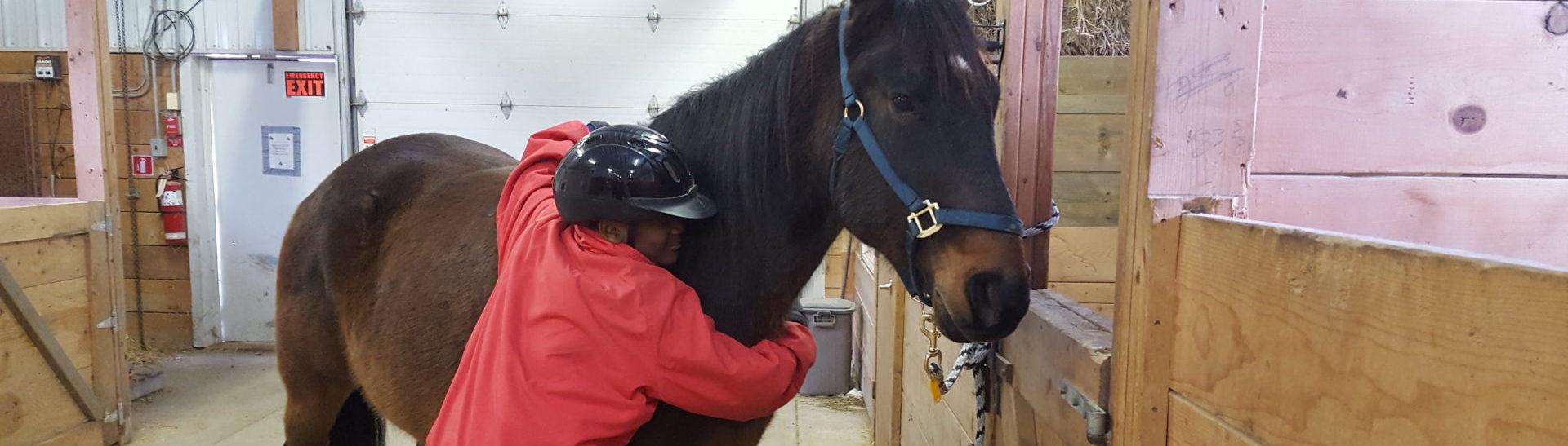 Student hugging horse