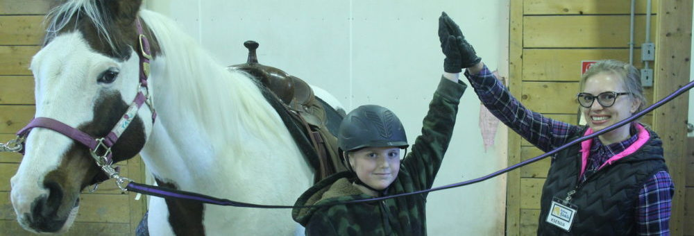 student high five with volunteer, next to horse