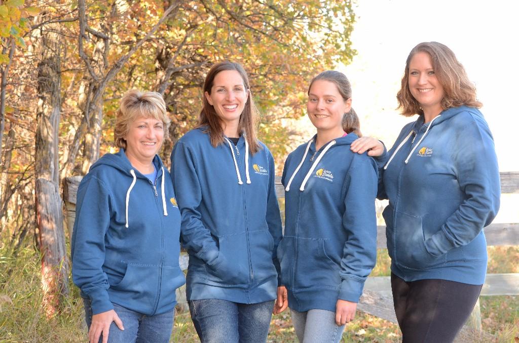 4 women wearing Urban Stable hoodies