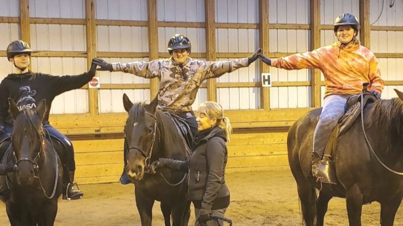 3 kids riding horses giving a high five